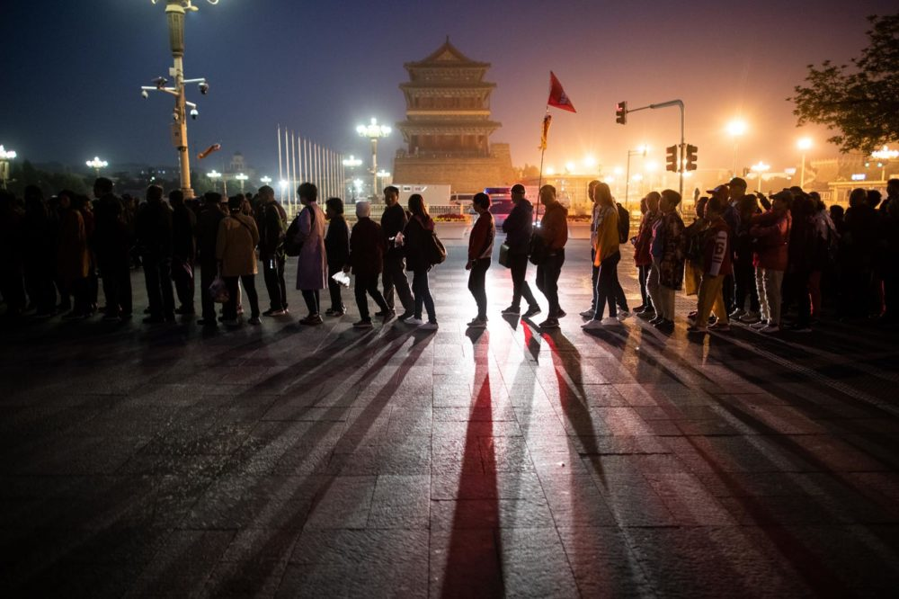In this picture taken on April 10, 2019, tourists line up for the flag-raising ceremony at Tiananmen Square in Beijing. (STR/AFP/Getty Images)