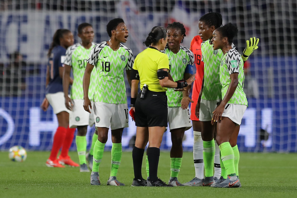 Nigeria players confront a referee after she awards France a penalty following a VAR review. (Richard Heathcote/Getty Images)