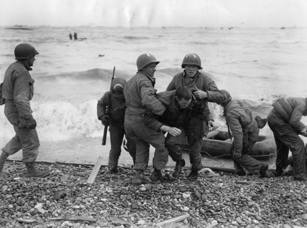 American troops helping their injured friends from a dinghy after the landing ship they were on was hit by enemy fire during the Allied invasion of France on D-Day. (Fox Photos/Getty Images)
