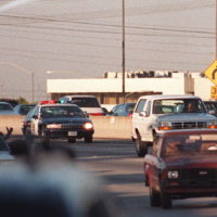 Motorists wave as police cars pursue the Ford Bronco (white, right) driven by Al Cowlings, carrying fugitive murder suspect O.J. Simpson, on a 90-minute slow-speed car chase June 17, 1994 on the 405 freeway in Los Angeles, Calif. (Mike Nelson/AFP/Getty Images)