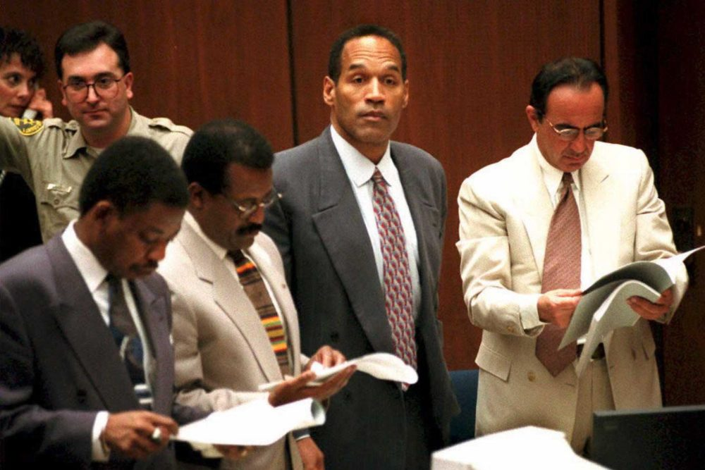 O.J. Simpson watches as the jury in his double-murder trial enters the courtroom, Feb. 2, 1995, in Los Angeles, Calif. His attorneys (left to right) Carl Douglas, Johnnie Cochran Jr. and Robert Shapiro look over documents. (Pool/AFP/Getty Images)