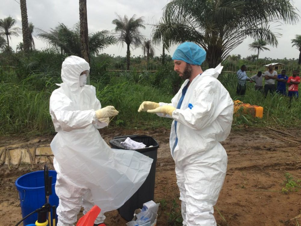 The author (right) puts on protective gear before helping remove waste from Princess Christian Maternity Hospital in Freetown, Sierra Leone, which PIH supported during the Ebola epidemic. (Courtesy Jonathan Lascher)