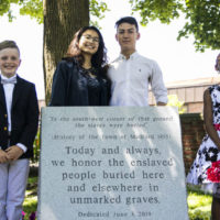 Medford Public Schools students Liam Brady, Jenny Lu, Joseph Schmidt and Jasmine Hagbourne stand for a photo at the unveiling ceremony of the Medford Slavery Memorial in Salem Street Burying Ground. The students organized the creation of a memorial to a group of more than 50 slaves who were buried in unmarked graves in the Salem Street Cemetery. (Erin Clark for WBUR)