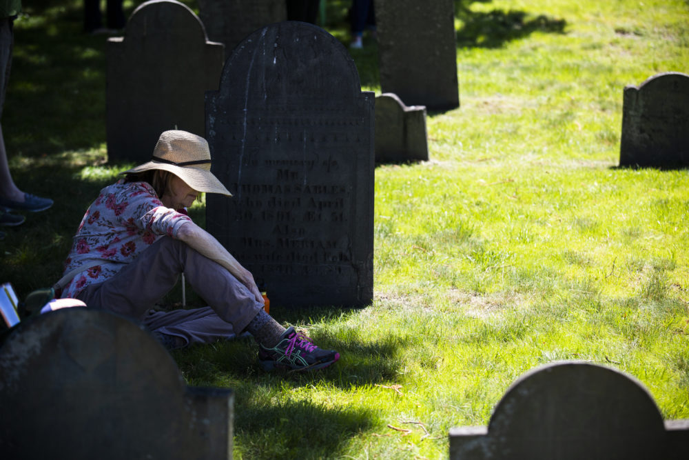 A woman sits in the shade at an unveiling ceremony of the Medford Slavery Memorial in Salem Street Burying Ground. (Erin Clark for WBUR)