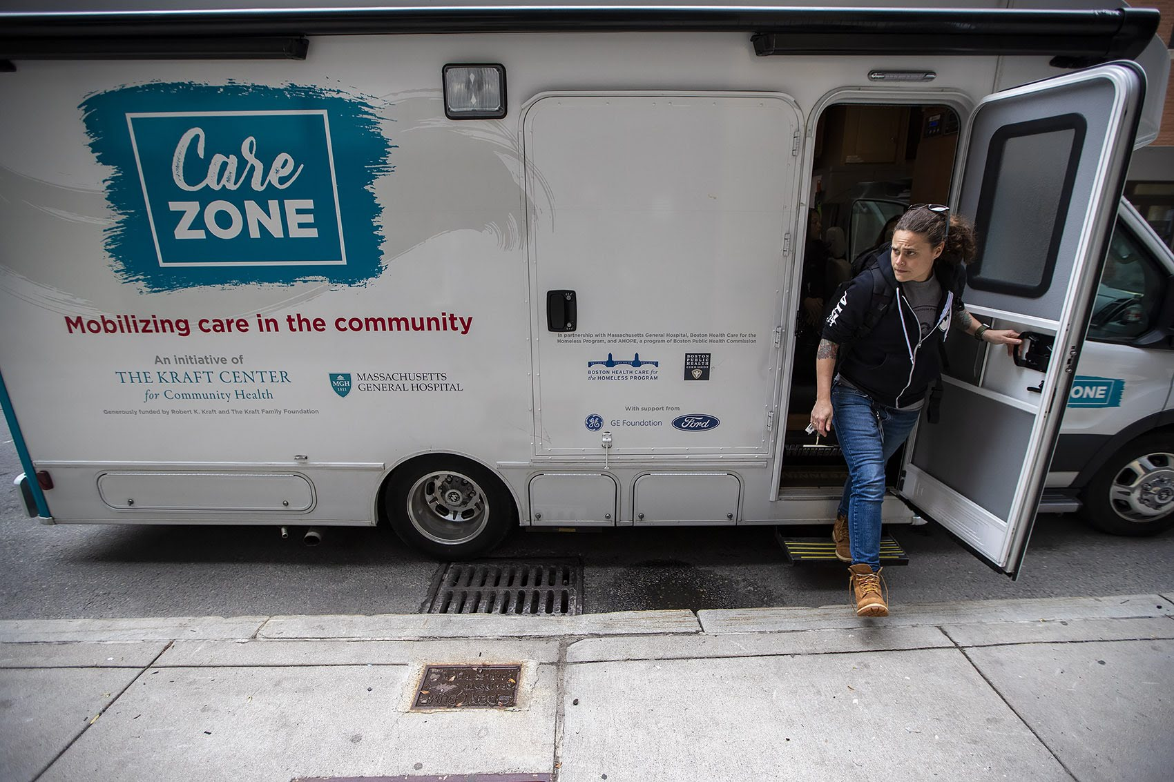 Sarah Mackin exits the Care Zone van after it parks on Haverhill Street near North Station. The outreach workers will walk around the area to look for opioid users who need assistance. (Jesse Costa/WBUR)