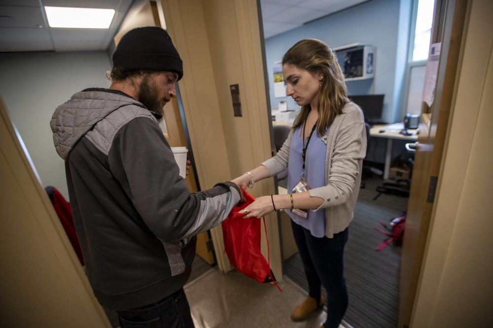 At the Boston Health Care for the Homeless office, case manager Samantha Walsh offers Cody a new backpack for what few belongings he has with him. (Jesse Costa/WBUR)