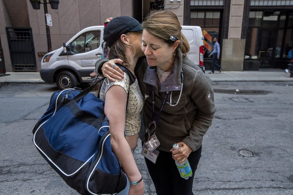 Jessie Gaeta give Bri a hug as she heads back out onto the streets at Downtown Crossing. (Jesse Costa/WBUR)