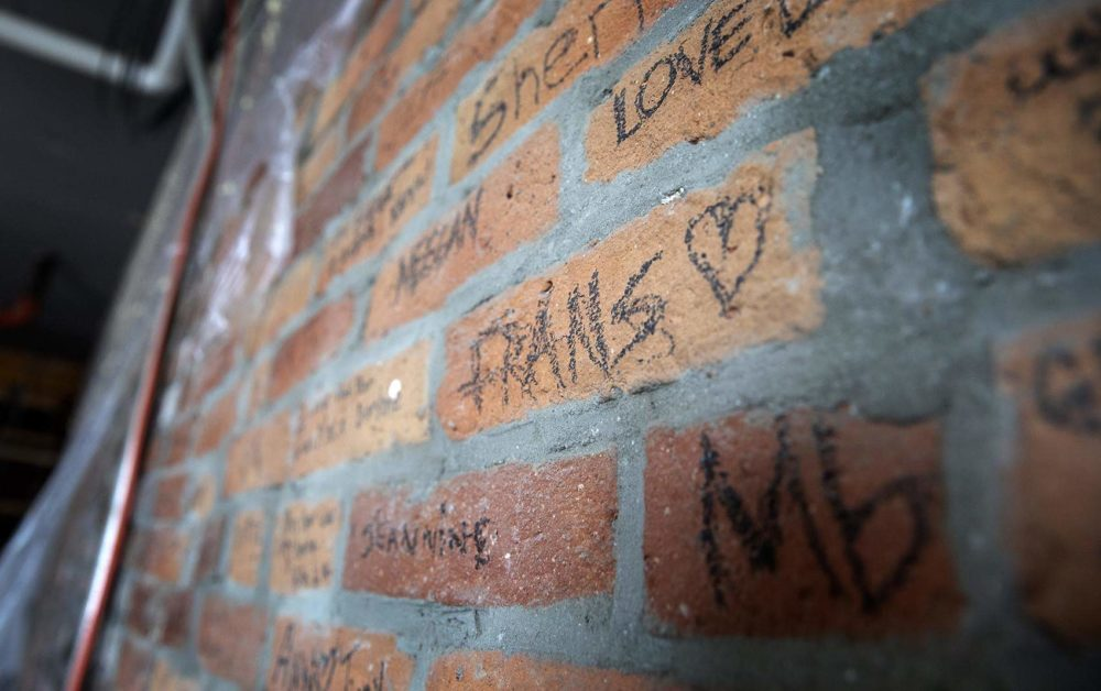 Names written on the brick wall when Fran's Place closed are still preserved today. (Robin Lubbock/WBUR)