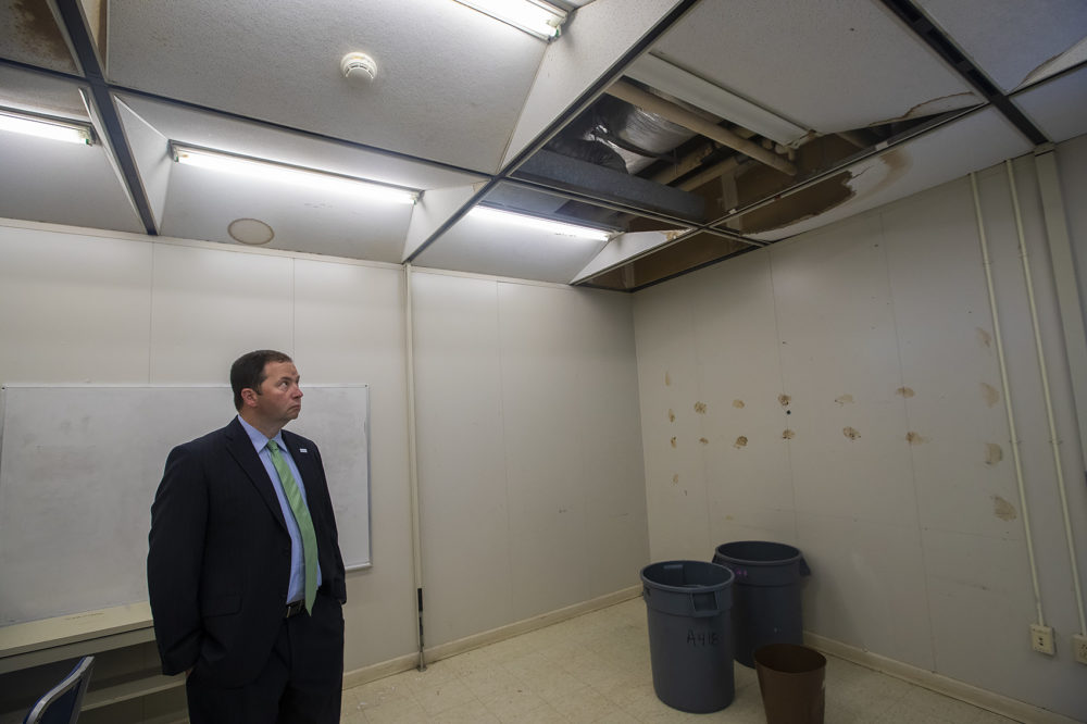 John Hanlon, chief of operations at BPS, looks at fallen ceiling tiles at the Horace Mann School for the Deaf and Hard of Hearing in Allston. (Jesse Costa/WBUR)