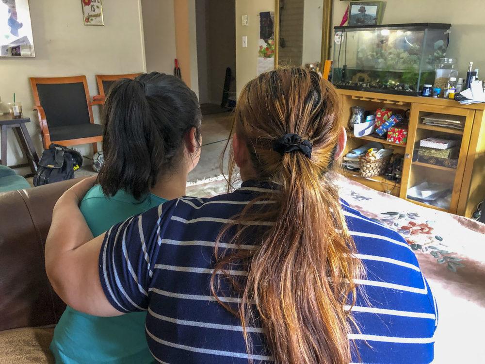 H holds her daughter M inside her home in Framingham, Mass. (Shannon Dooling/WBUR)