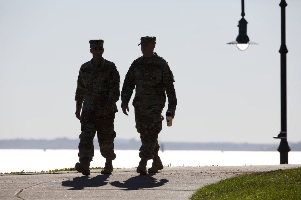 Two soldiers from the 1st 101st Field Artillery of the Massachusetts National Guard walk at Castle Island in Boston in 2017. (Michael Dwyer/AP)
