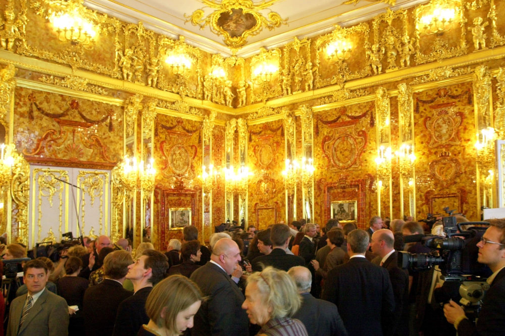 Visitors look at the Amber Room in the Catherine Palace near St. Petersburg, Russia,  as the restored chamber was presented to reporters. (AP Photo/ Dmitry Lovetsky)