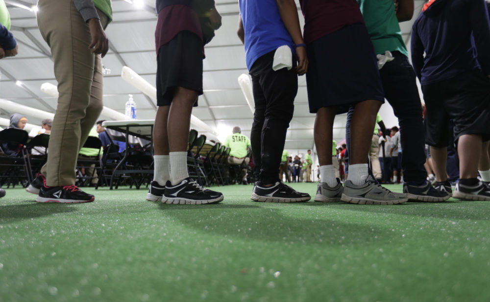 In this July 9, 2019 photo, immigrants line up in the dinning hall at the U.S. government's newest holding center for migrant children in Carrizo Springs, Texas. (Eric Gay/AP)