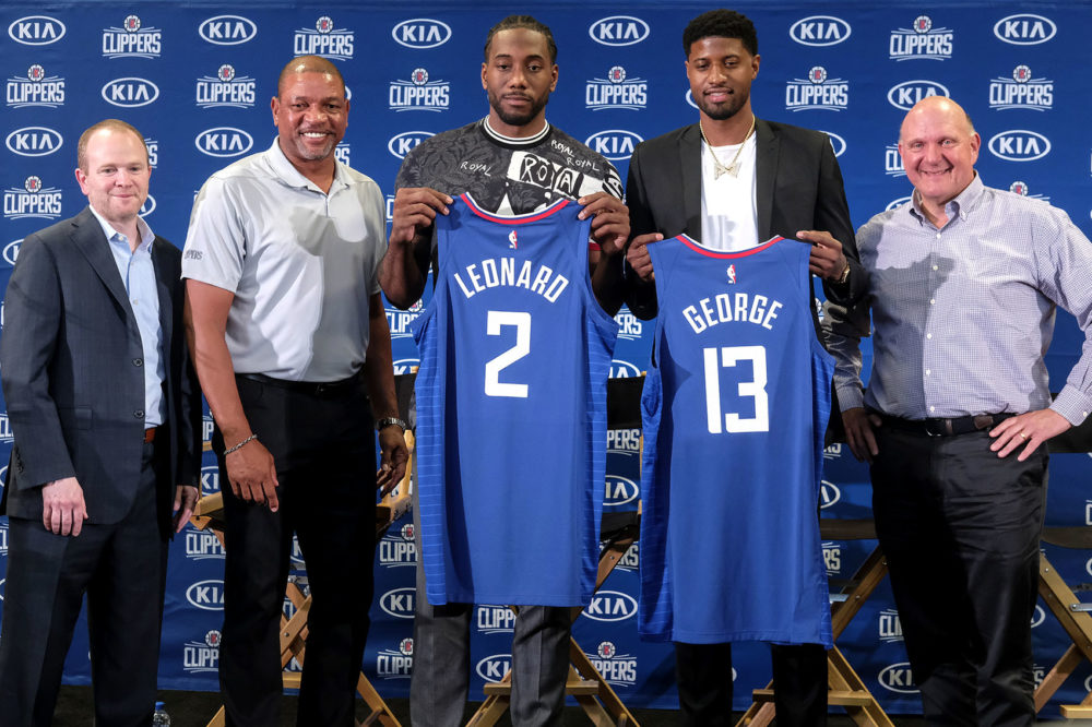 Kawhi Leonard, center, and Paul George, second from the right, holding their new team jerseys, pose with Los Angeles Clippers President of Basketball Operations Lawrence Frank, left, head coach Doc Rivers, second from the left, and team chairman Steve Ballmer during a press conference in Los Angeles, Wednesday, July 24, 2019. (Ringo H.W. Chiu/AP)