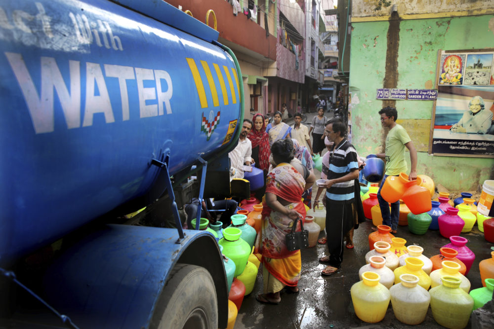 In this Monday, July 15, 2019, photo, people fill drinking water from a water tanker truck in Chennai, in the Southern Indian state of Tamil Nadu. Demand for water in India's Motor City, a manufacturing and IT hub on the Bay of Bengal, far outstrips supply, forcing authorities to take extreme and costly measures to deliver potable water to its residents. (Manish Swarup/AP)