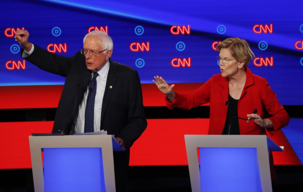 Sen. Bernie Sanders, I-Vt., and Sen. Elizabeth Warren, D-Mass., talk during in the first of two Democratic presidential primary debates hosted by CNN Tuesday, July 30, 2019, in the Fox Theatre in Detroit. (Paul Sancya/AP)