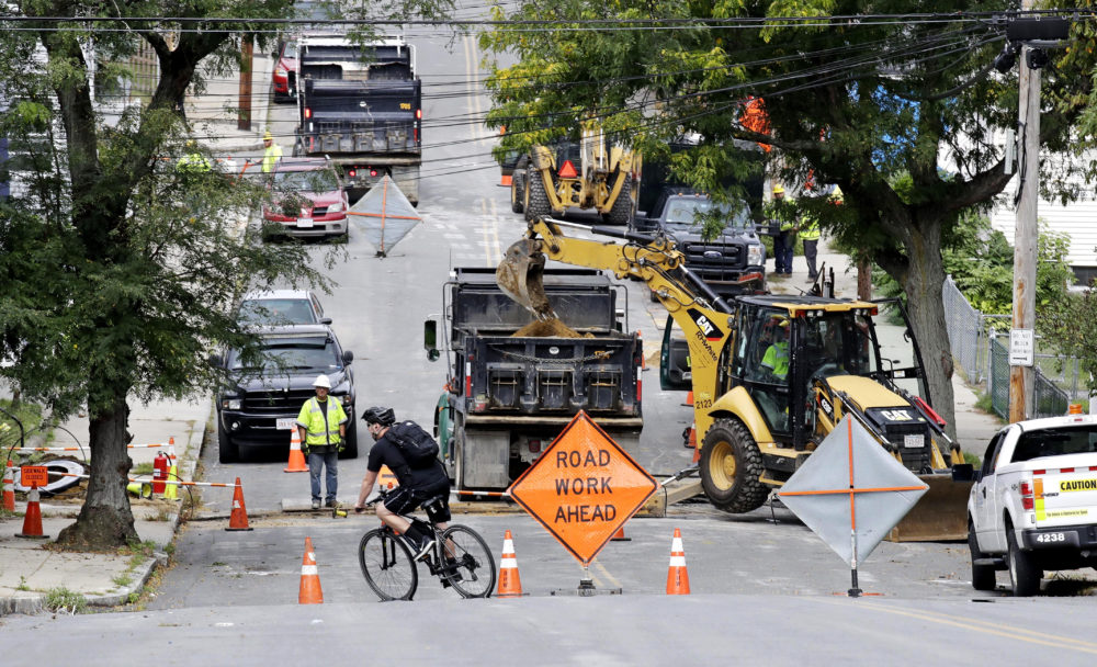 A bicyclist takes a turn at a road block as utility contractors dig up the road above natural gas lines along Brookfield Street in Lawrence, Mass. in September 2018. (Charles Krupa/AP)
