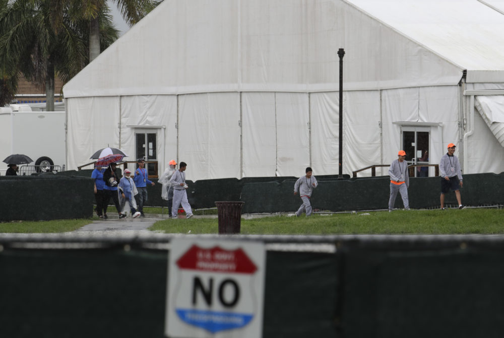 Migrant children and employees walks on the grounds of the Homestead Temporary Shelter for Unaccompanied Children on June 16 in Homestead, Fla. (Lynne Sladky/AP)
