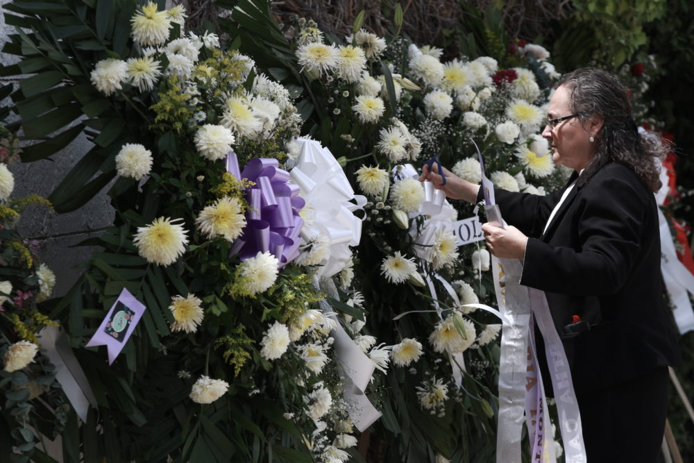 A woman places a ribbon on a flower arrangement, at the funeral of elementary school principal Elsa Mendoza, of one of the 22 people killed in a shooting at a Walmart in El Paso, in Ciudad  Juarez, Mexico, on Aug. 8. (Christian Chavez/AP)