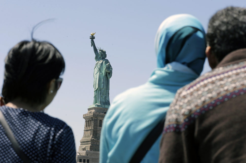 In this May 7, 2015, file photo, people look at the Statue of Liberty from a ferry boat in Jersey City, N.J. (Mel Evans/AP)