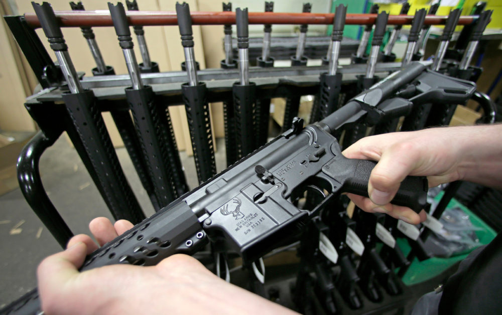In this April 10, 2013 file photo, craftsman Veetek Witkowski holds a newly assembled AR-15 rifle at the Stag Arms company in New Britain, Conn. (Charles Krupa/AP)