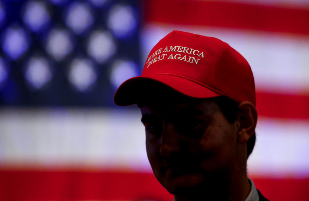 Oliver Lester, of Montgomery, Ala., wears a hat with President Trump's campaign slogan as he watches results come in for Gov. Kay Ivey at a watch party on Nov. 6, 2018, in Montgomery. (Butch Dill/AP)