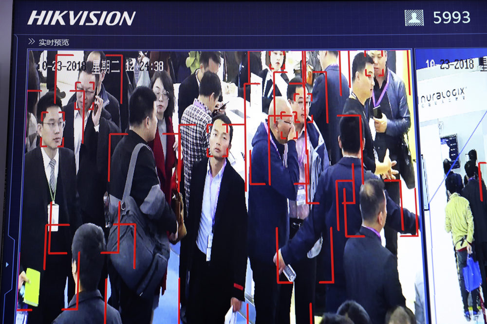 In this photo taken Tuesday, Oct. 23, 2018, visitors are tracked by facial recognition technology from state-owned surveillance equipment manufacturer Hikvision at the Security China 2018 expo in Beijing, China. The Chinese video surveillance company says it is taking concern about the use of its technology seriously following a report that the U.S. may block several Chinese surveillance companies from buying American components. (Ng Han Guan/AP)