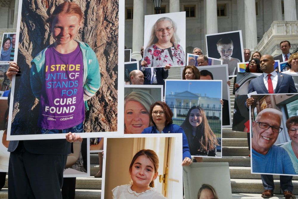 Sen. Tammy Duckworth, D-Ill., center, attends a news conference on health care among photos of people with preexisting conditions at the Capitol on July 9 in Washington. At right is Rep. Colin Allred, R-Texas. (Jacquelyn Martin/AP)