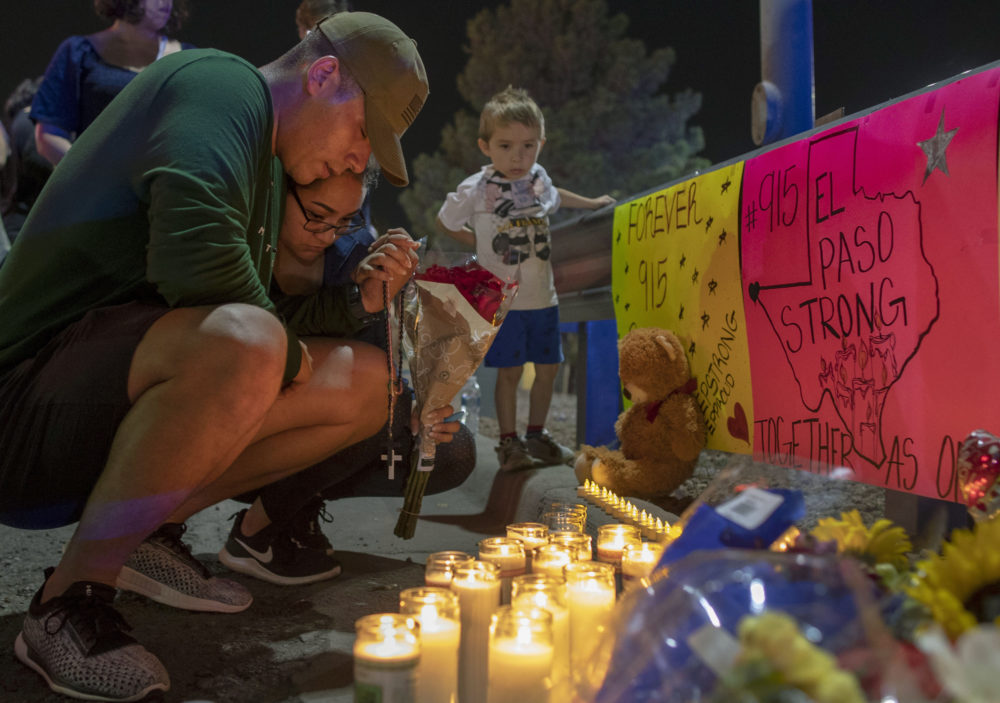 Rene Aguilar and Jackie Flores pray at a makeshift memorial for the victims of Saturday's mass shooting at a shopping complex in El Paso, Texas, Sunday, Aug. 4, 2019. (Andres Leighton/AP)