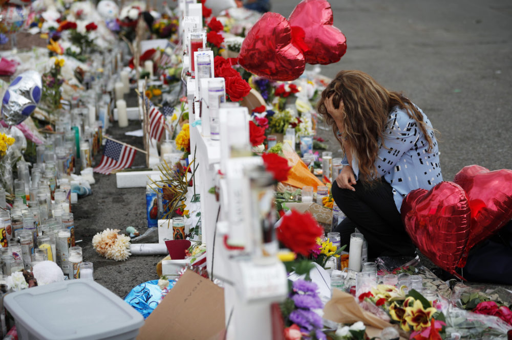Gloria Garces kneels in front of crosses at a makeshift memorial near the scene of a mass shooting at a shopping complex Tuesday, Aug. 6, 2019, in El Paso, Texas. (AP/John Locher)