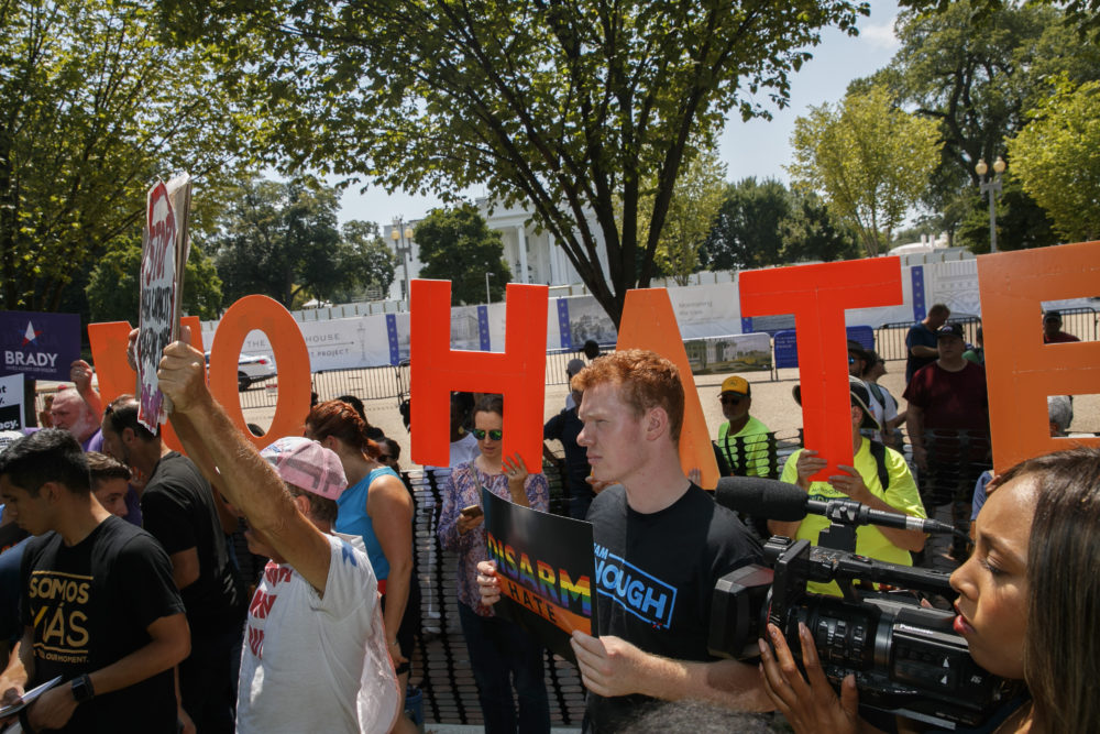 "Adam Friedman, 19, a youth organizer with the Brady Campaign To Prevent Gun Violence, holds a sign saying ""Disarm Hate""  during a rally against racism, and in favor of gun laws on Aug. 6 in Washington. (Jacquelyn Martin/AP)"