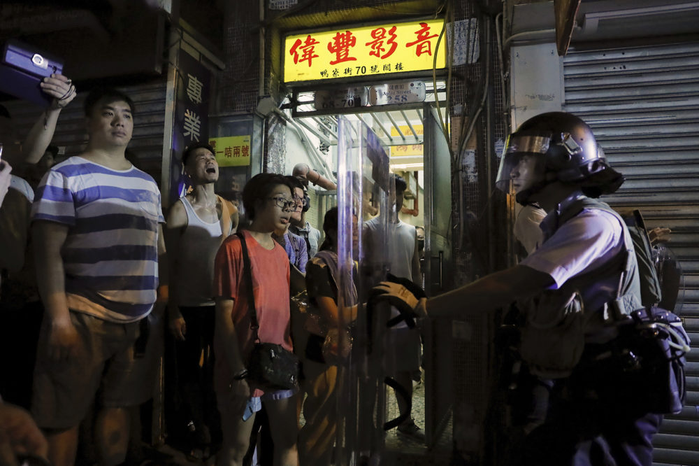 Residents watch policemen arresting people on a street during a face off at Sham Shui Po district in Hong Kong, Wednesday, Aug. 7, 2019. (Kin Cheung/AP)