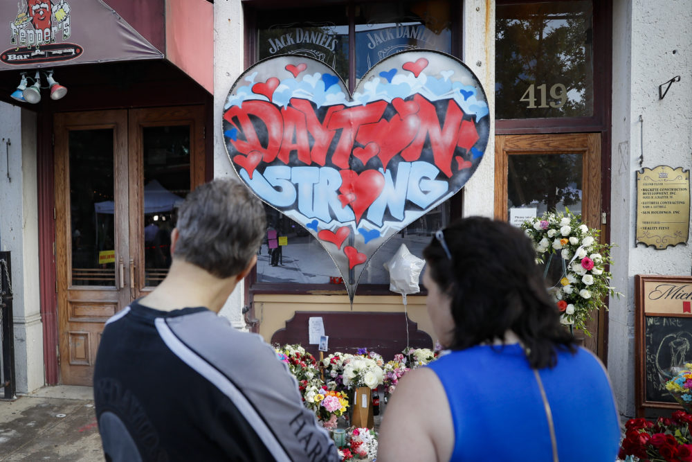 Mourners last week visit a makeshift memorial for the slain and injured victims of a mass shooting that occurred in the Oregon District in Dayton, Ohio. (John Minchillo/AP)