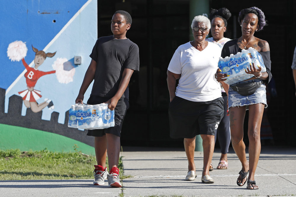 Rahjiah McBride, of Chester, Pa., right, helps her relatives, Newark residents Elnora and Bowdell Goodwin, center and second right, as Goodwin's son pitches in carrying bottled water from the Boylan Street Recreation Center, Monday, Aug. 12, 2019, in Newark, N.J. (Kathy Willens/AP)