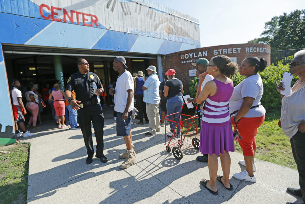 "A line forms in front of the Bolan Street Recreation center as Newark residents picked up cases of bottled water, Monday, Aug. 12, 2019, in Newark, N.J., after U.S. Environmental Protection Agency revealed that recent tests showed elevated lead levels in drinking water in a few locations despite filters that had been distributed earlier. The EPA warned that ""out of an abundance of caution"" residents should use bottled water for drinking and cooking. People exiting the facility said they had waited two to three hours for the water. (Kathy Willens/AP)"