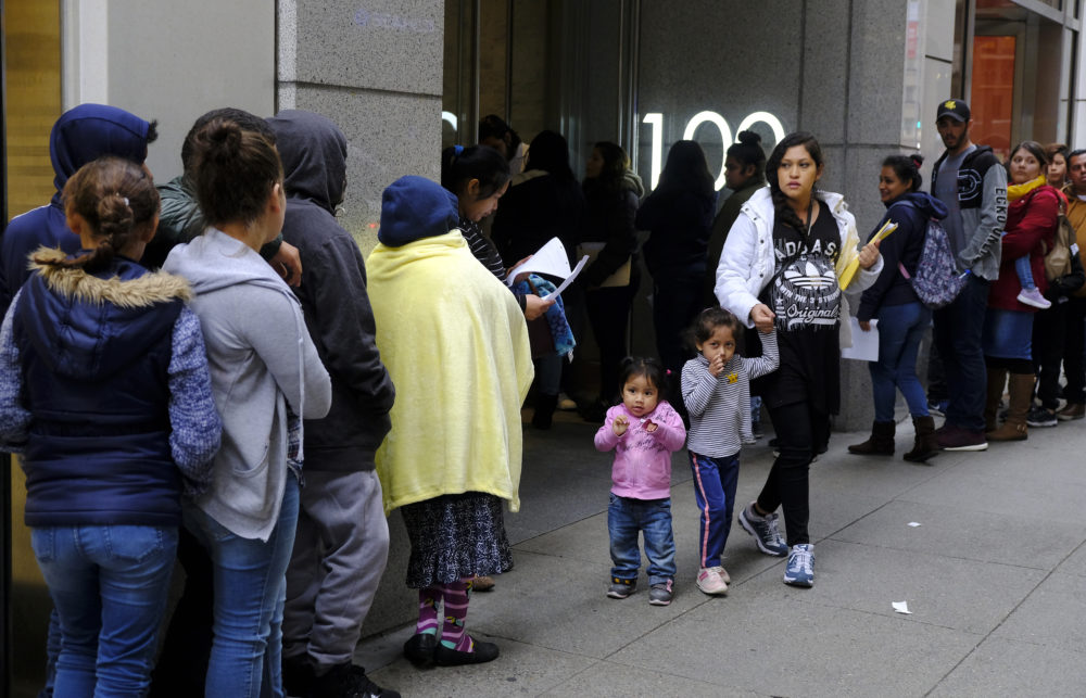 """In this Jan. 31, 2019, file photo, hundreds of people overflow onto the sidewalk in a line snaking around the block outside a U.S. immigration office with numerous courtrooms in San Francisco. Santa Clara and San Francisco have filed suit against the Trump administration over its new controversial """"public charge"""" rule that restricts legal immigration. This lawsuit is the first after the Department of Homeland Security's announcement Monday, Aug. 12, 2019, that it would deny green cards to migrants who use Medicaid, food stamps, housing vouchers or other forms of public assistance. (Eric Risberg/AP)"""