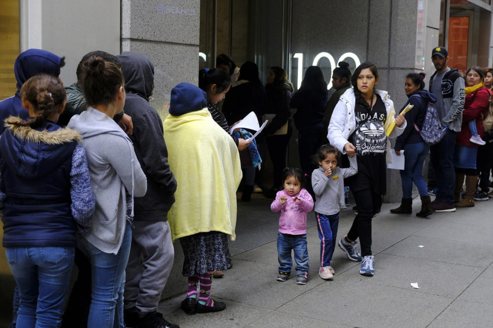 In this Jan. 31, 2019, file photo, hundreds of people overflow onto the sidewalk in a line snaking around the block outside a U.S. immigration office with numerous courtrooms in San Francisco. (Eric Risberg, File/AP)