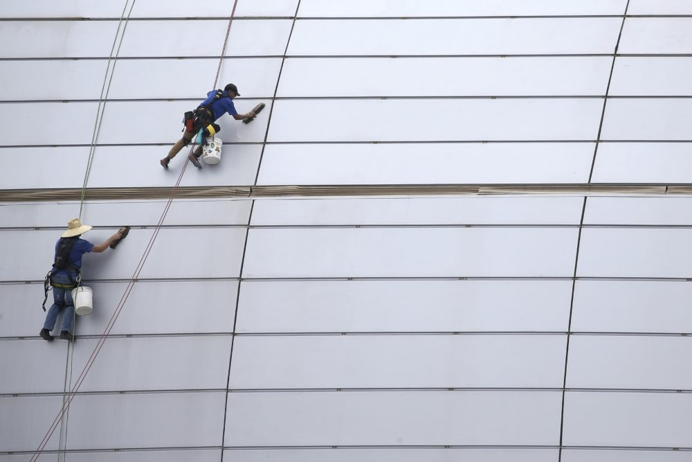 In this July 31, 2019, file photo workers clean the outside facade of State Farm Stadium in Glendale, Ariz. The shareholder comes first has for years been the mantra of the Business Roundtable, a group representing the most powerful CEOs in America. The group on Monday, Aug. 19, released a new mission statement that implies a foundational shift; a step back from shareholder primacy. (Ross D. Franklin/AP)