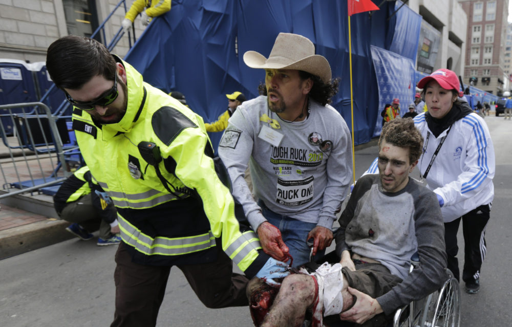 An emergency responder and volunteers, including Carlos Arredondo, in the cowboy hat, push Jeff Bauman in a wheelchair after he was injured in one of two explosions near the finish line of the Boston Marathon. (Charles Krupa/AP/File)