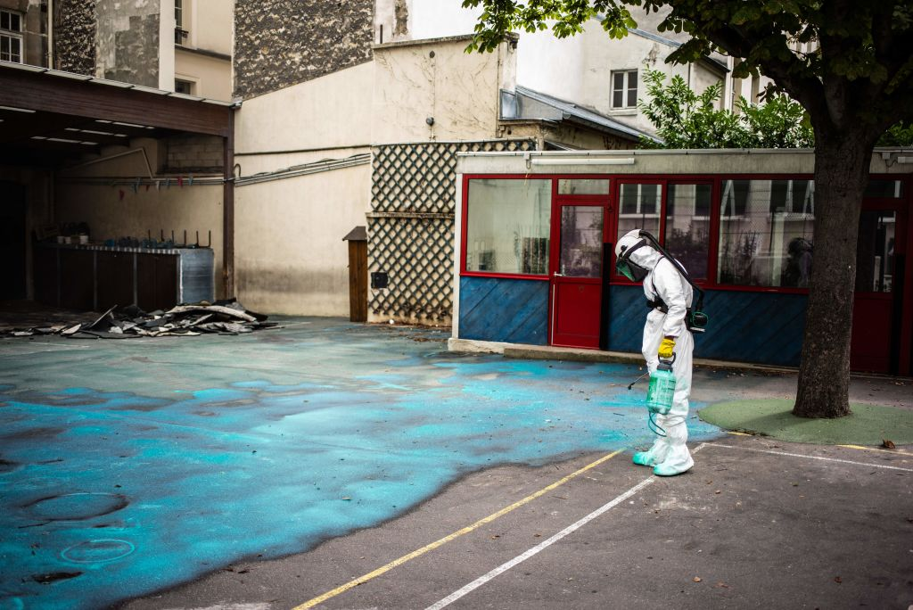 A worker sprays a gel on the ground to absorb lead as he takes part in a clean-up operation at Saint Benoit school near Notre Dame cathedral during a decontamination operation on August 8, 2019. (Martin Bureau/AFP/Getty Images)