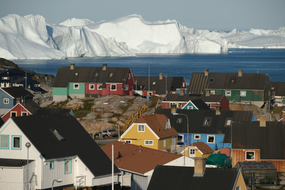 Icebergs floating at the mouth of the Ilulissat Icefjord loom behind the town center on July 30, 2019 in Ilulissat, Greenland. (Sean Gallup/Getty Images)