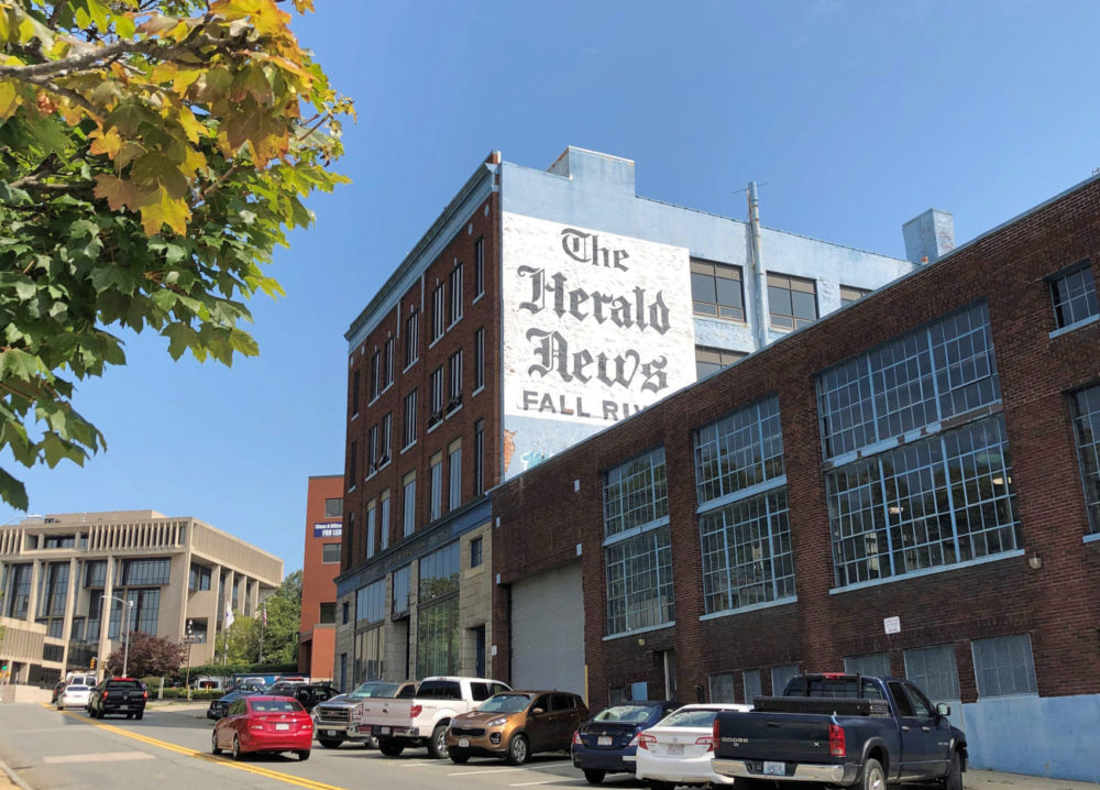 The Herald News' proximity to Fall River Government Center, left, makes it easy for reporters to keep an eye on public officials. But recent cuts at the GateHouse-owned daily have left a newsroom staff in the single digits. (Callum Borchers/WBUR)