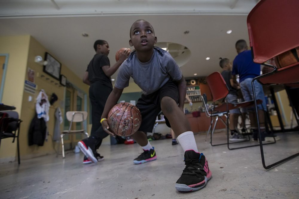 Nine-year-old Devin Miller bounces his decorated basketball between his legs during an old basketball decorating/collection event at the Yawkey Boys and Girls Club in Roxbury. (Jesse Costa/WBUR)