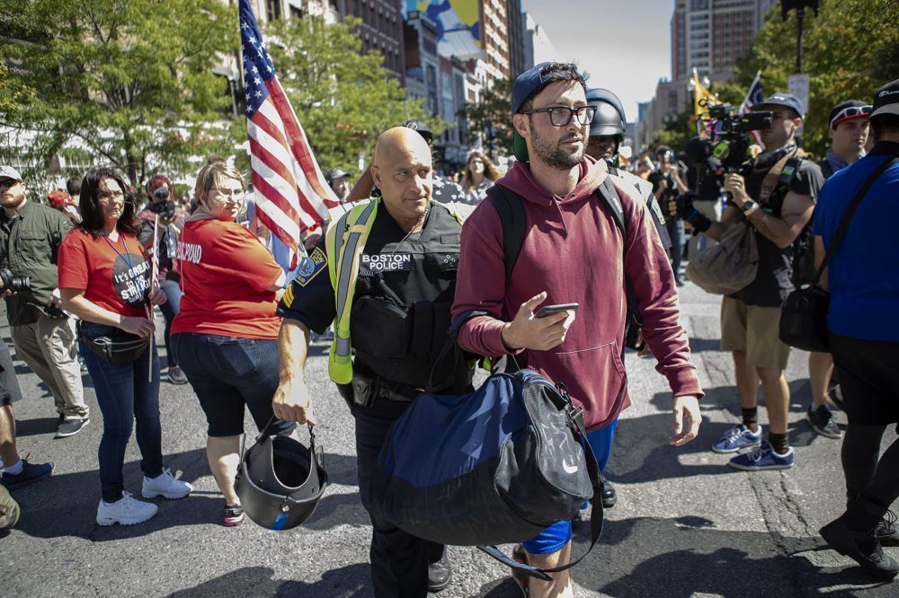 "A counter-protester is escorted by a Boston police officer during the ""Straight Pride"" parade. (Jesse Costa/WBUR)"