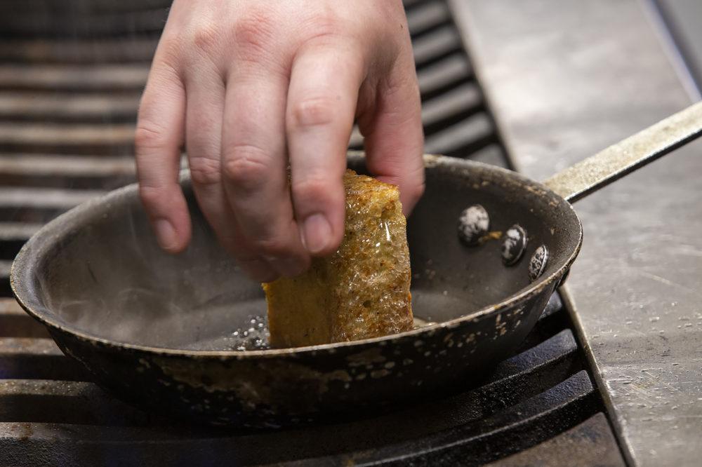 Chef Michael Morway grilling a piece of his Plimoth Cornbread, a part of a popular burrata dish on the Trillium menu. (Jesse Costa/WBUR)