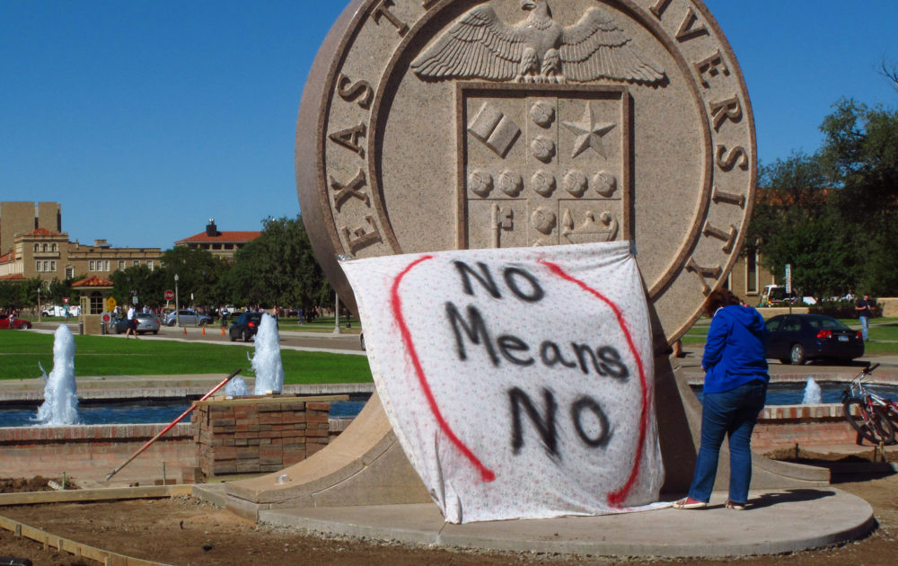 "In this 2014 photo, a student helps drape a bed sheet with the message ""No Means No"" over the university's seal at the Lubbock, Texas campus in a demonstration against sexual violence on campus. (Betsy Blaney/AP)"