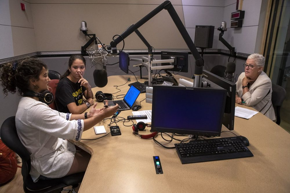 Saya Ameli Hajebi, left and Audrey Lin speak with former head of the Environmental Protection Agency Gina McCarthy at the WBUR studios. (Jesse Costa/WBUR)