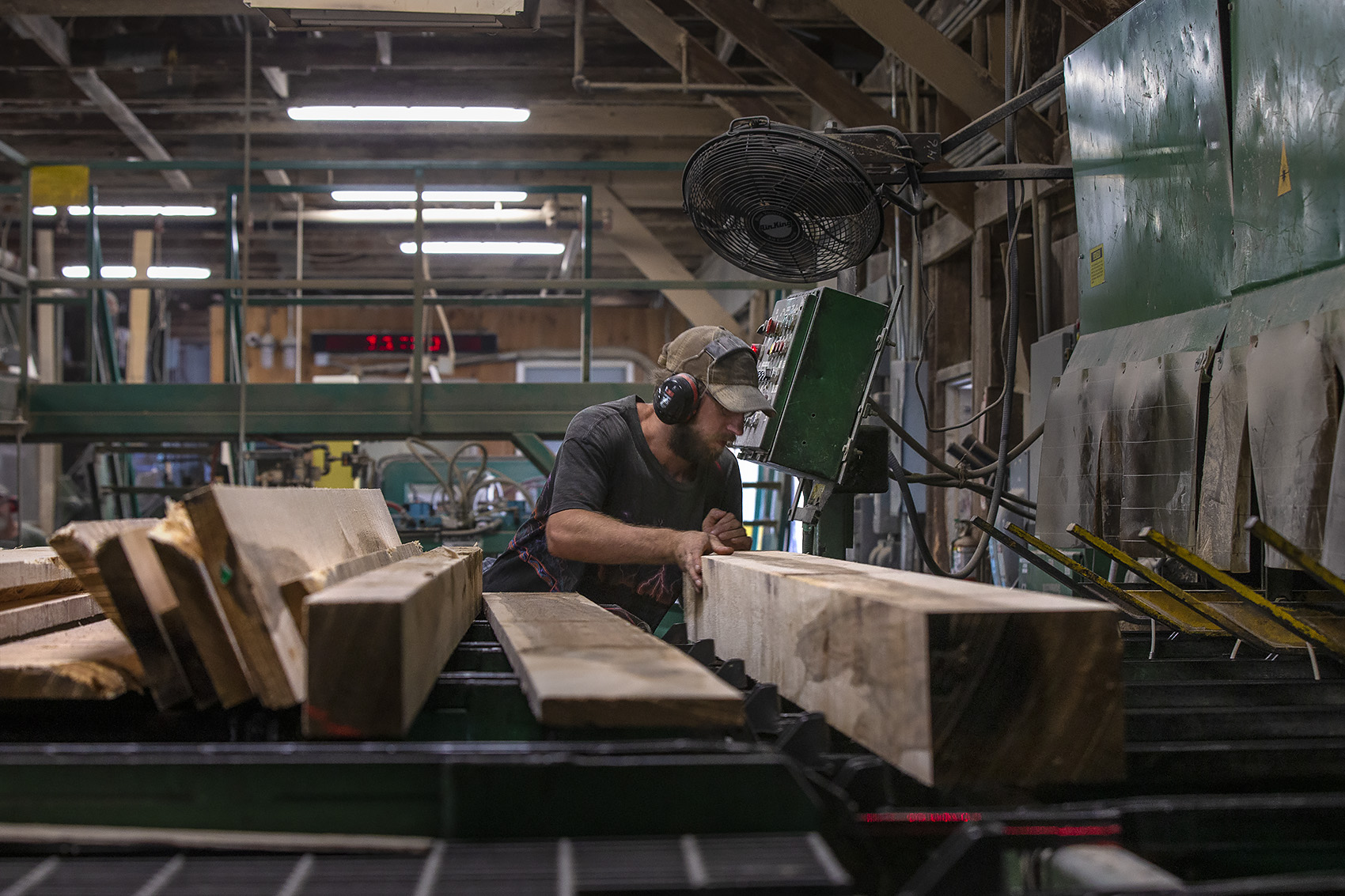 An employee inspects oak boards before they are sorted at Allard Lumber in Brattleboro, Vermont. (Jesse Costa/WBUR)