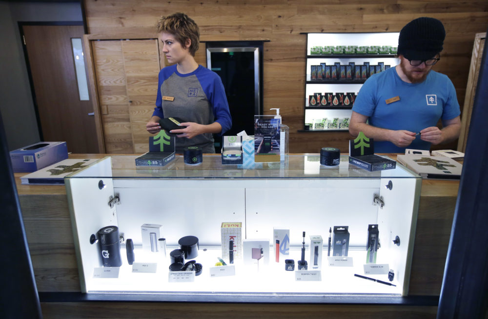 Patient service associates Savannah Stuitje, left, and Josh Hirst, right, stand at a counter that features a display of vape dispensers that could be used for legal recreational cannabis, at New England Treatment Access medical marijuana dispensary (Steven Senne/AP File Photo)