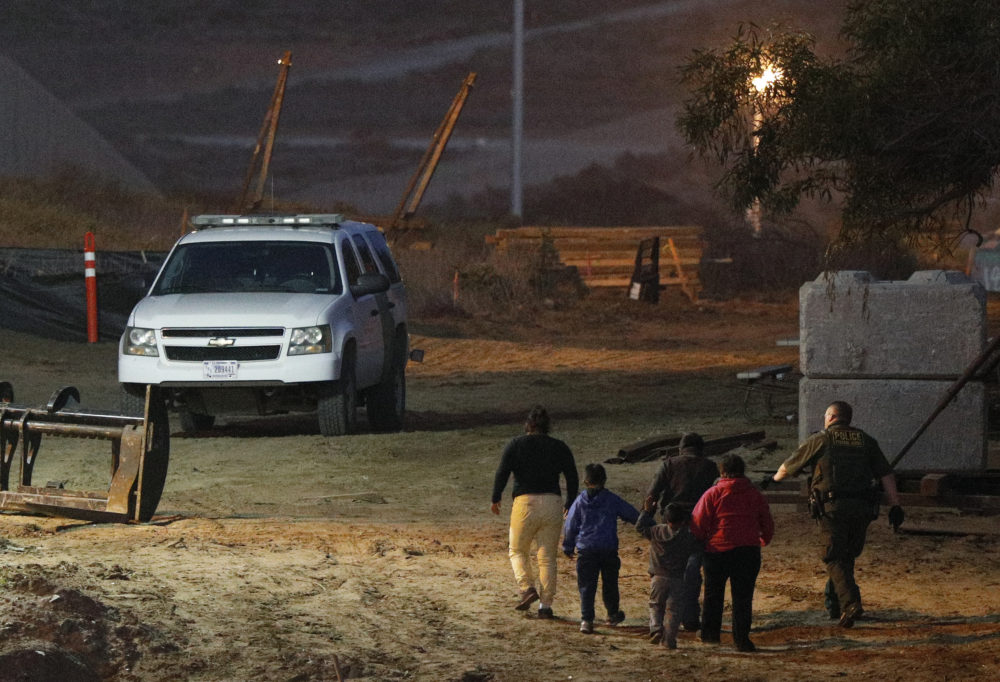 In this Dec. 3, 2018 file photo, migrants are escorted by a U.S. Border Patrol agent as they are detained after climbing over the border wall from Playas de Tijuana, Mexico, to San Ysidro, Calif.  (Rebecca Blackwell/AP)
